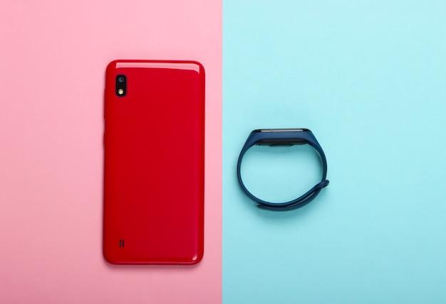 現代のガジェット。ピンクブルーのスマートフォンとスマートブレスレット