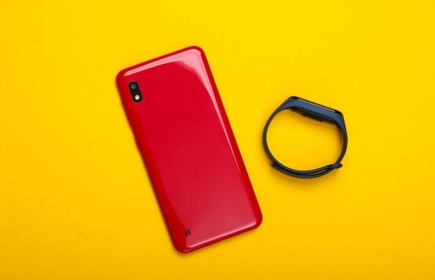 現代のガジェット。黄色のスマートフォンとスマートブレスレット