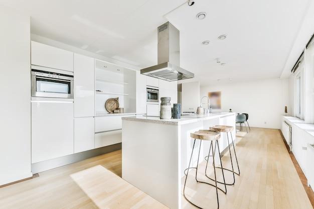 흰 벽이있는 스튜디오 다락방 아파트의 나무 캐비닛과 미니멀리스트 디자인의 현대식 조리실 주방