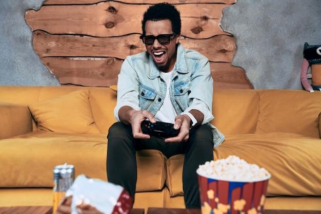 現代のゲーマー。ビデオゲームをプレイし、家で時間を過ごしながら顔を作るカジュアルな服装で欲求不満の若い男