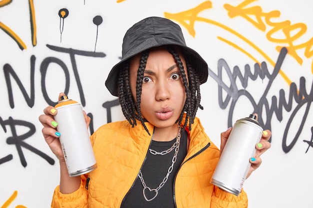 Modern generation concept. surprised trendy afro american woman has crazy style holds aerosol spray cans for drawing graffiti on street wall wears trendy outfit