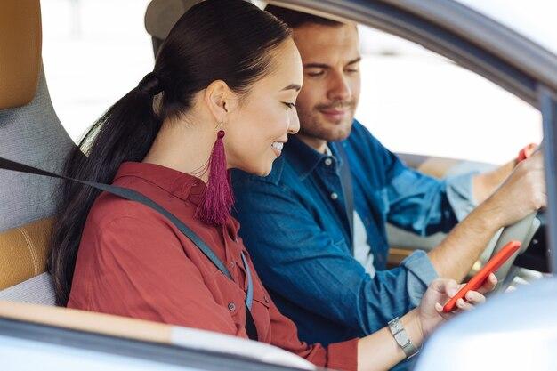 現代の世代。彼女のボーイフレンドと一緒に車に座っている間彼女のスマートフォンを使用して喜んでいるアジアの女性