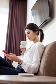 Modern generation. pleasant smart woman looking at the smartphone screen while drinking coffee