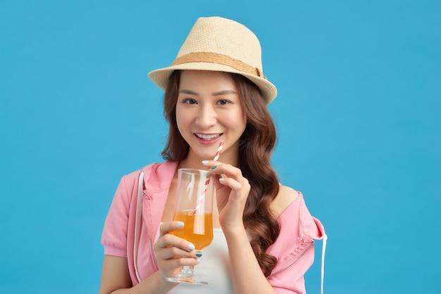 オレンジジュースを飲む現代の女の子。孤立した肖像画。