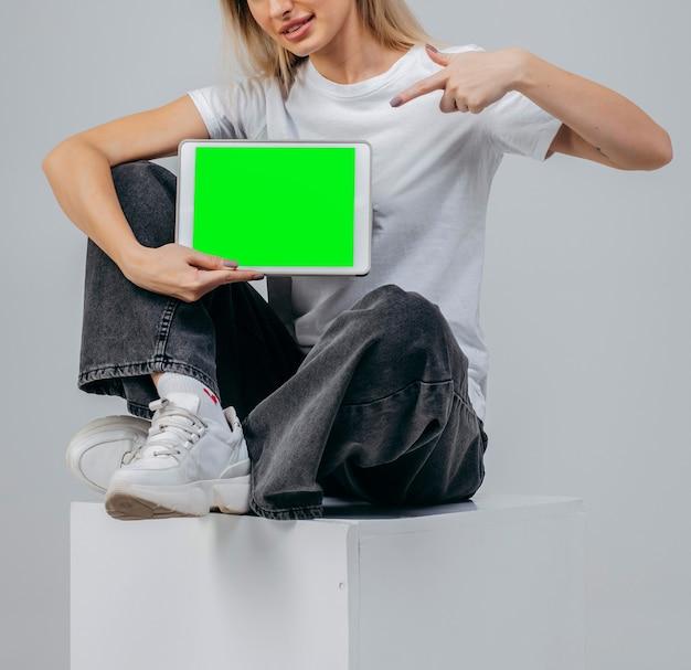スタジオでタブレットと白いtシャツのモダンな女の子無料の創造性