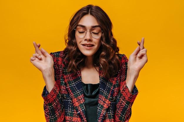 Ragazza moderna con i capelli castani in abito a righe incrociando il dito sul muro isolato