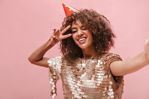 现代女孩卷发蓬松的发型在米色美丽的裙子显示和平的标志,眨眼,并在粉红色的墙上自拍。