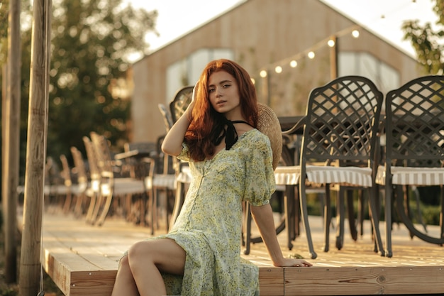 Modern girl with freckles, black bandage on neck and ginger hairstyle in summer stylish dress looking at front in a cafe terrace