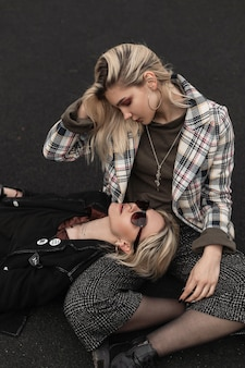 Modern girlfriends in black clothes in sunglasses lies on lap of friend in plaid jacket