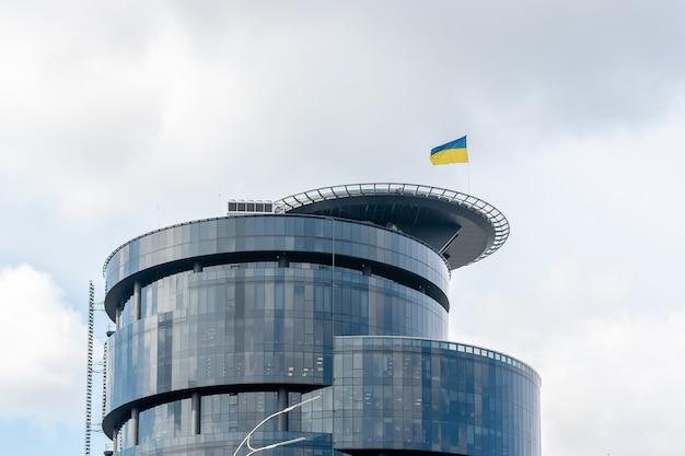 우크라이나 국기가 있는 현대적인 유리 및 철강 사무실 건물.