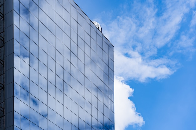 Modern glass building architecture with blue sky and clouds