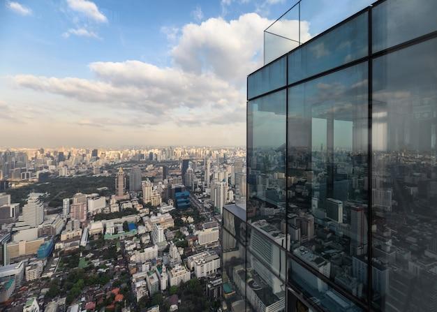 青い空とバンコクの街の混雑したダウンタウンのモダンなガラスの建物
