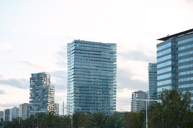Modern glass and concrete city buildings minutes after sunset against clear white sky