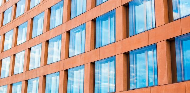 オフィスビルのモダンなガラスのファサード、窓の空の反射。