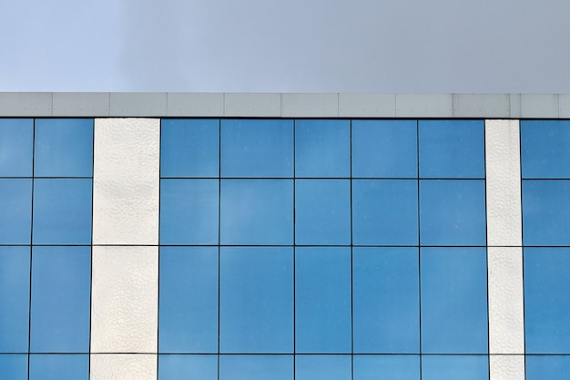 Современное стеклянное офисное здание с фоном голубого неба. стена здания финансового офиса банка. недвижимость.