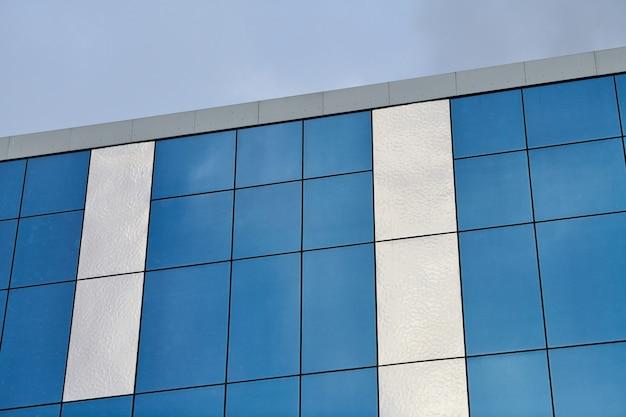 Современное стеклянное офисное здание с голубым небом