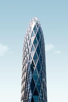 青空の下でガラス張りのモダンな高層ビル