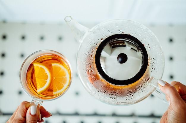 モダンなガラスのティーポットとレモン入りのお茶のコップ。茶道のコンセプト。