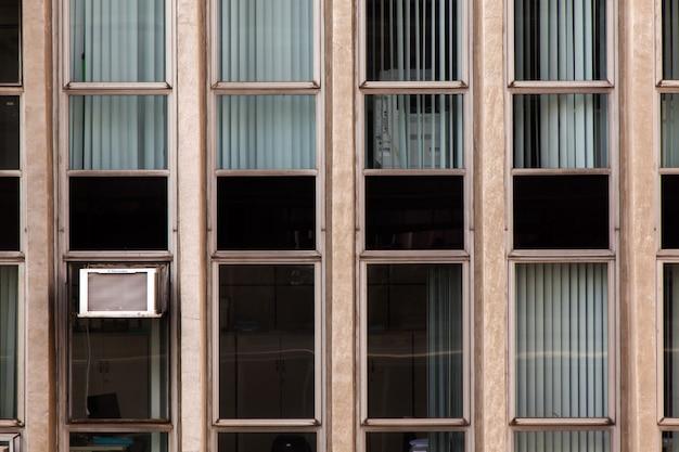 コンクリートの建物のファサードのモダンなガラス窓-都市近代建築