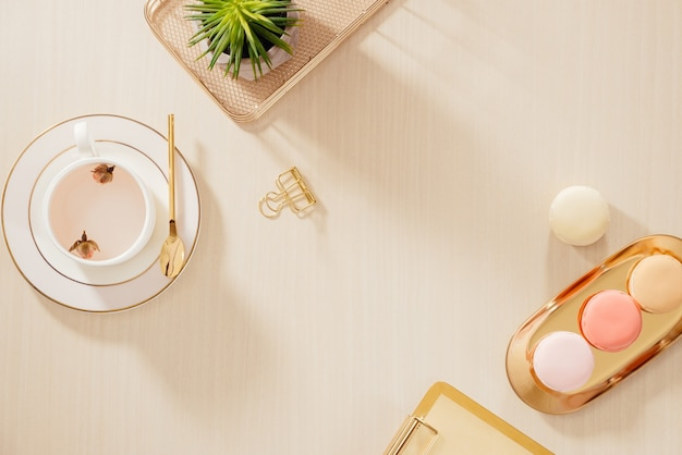 Modern gold stylized home office desk with folder, macaroons, coffee mug on beige background. flat lay, top view lifestyle concept.`