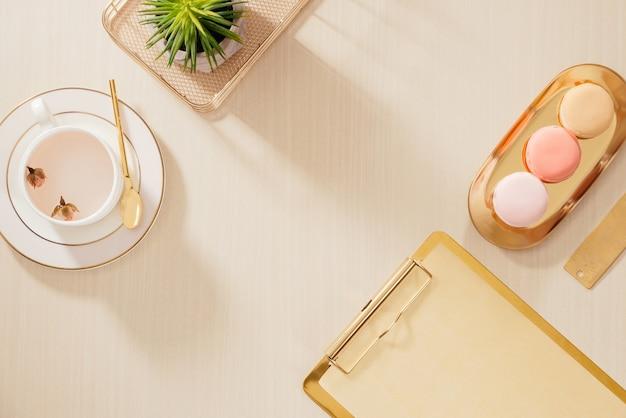 フォルダー、マカロン、ベージュの背景にコーヒーマグを備えたモダンなゴールドの様式化されたホームオフィスデスク。フラットレイ、トップビューのライフスタイルコンセプト。`