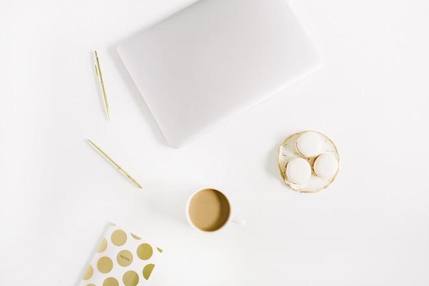 白い背景にラップトップ、マカロン、ペン、コーヒー マグを備えた、現代の金の様式化されたホーム オフィス デスク。フラットレイ、トップビュー