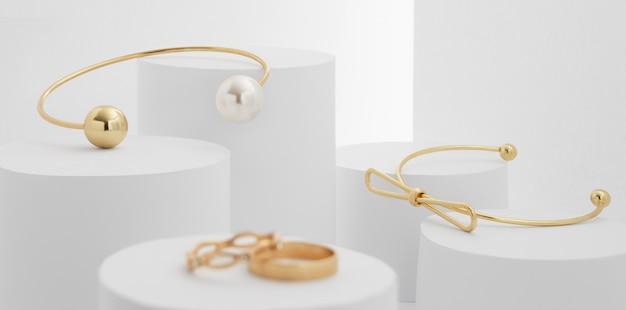 Modern golden bracelets with pearl on white blocks