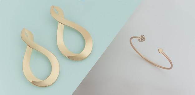 Современные золотые серьги и браслет на синем и белом фоне