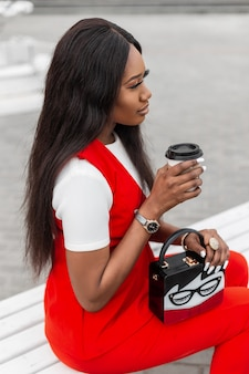 街の屋外のベンチに座っている手にコーヒーとスタイリッシュなハンドバッグと赤の美しいスーツを着たモダンでゴージャスな若い黒人女性。かわいいトレンディなアフリカの女の子のファッションモデルは、路上でホットドリンクを飲みます。