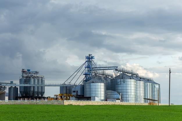 Современный элеватор зернохранилища и линия очистки семян. серебряные силосы на агроперерабатывающем и производственном предприятии для хранения и переработки сушильной очистки сельскохозяйственной продукции, муки, круп и зерна.