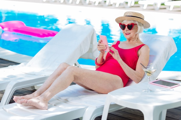 Modern grandmother wearing bright red swimming suit lying on deck chair near outside pool