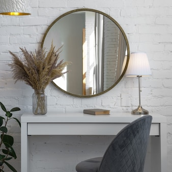 Modern gray velvet chair desk round mirror and table lamp and home accessories with copy space