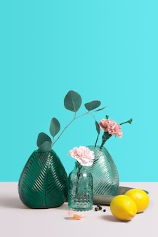 Modern green glass vase with beautiful pink flowers. creative composition with flowers, lemon and vase on blue background. minimalism with copy space for text or design. concept for flower shop