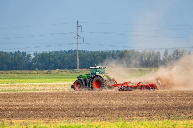 Modern green tractor plows the land before sowing