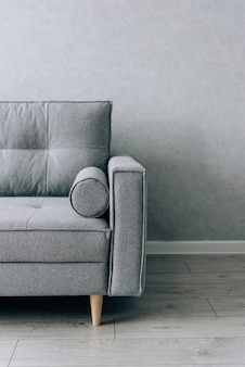 Modern grey sofa with wooden legs in the room
