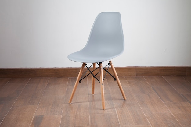 Modern grey and wood chair isolated on wooden floor and white chair