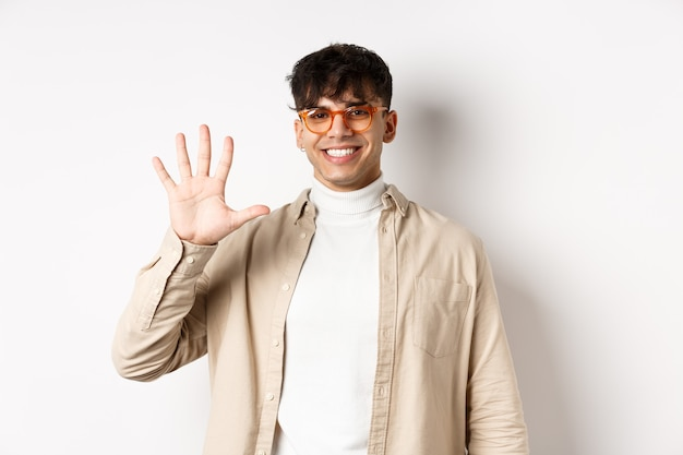 Modern guy in glasses and stylish outfit, showing five fingers number and smiling, making order, standing on white background
