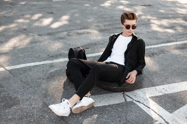 검은 색 트렌디 한 배낭이 달린 검은 색 선글라스에 세련된 우아한 검은 옷을 입은 현대 남자 모델이 거리에 앉아 있습니다.
