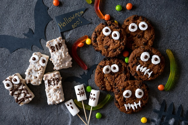 Modern halloween background. halloween candy bar: funny monsters made of biscuits with chocolate and ghosts marshmelow close-up on the table