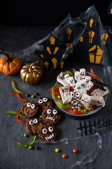 現代のハロウィーンの背景。ハロウィーンのキャンディーバー:ビスケットとチョコレートとゴーストマーシュメローテーブルのクローズアップで作られた面白いモンスター