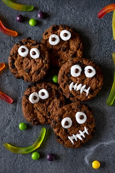 Modern halloween background. halloween cookies. funny monsters made of biscuits with chocolate on the table