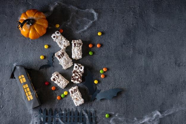 Современный фон хэллоуина. печенье на хэллоуин. забавные монстры из печенья с шоколадом на столе. украшение вечеринки в честь хэллоуина. кошелек или жизнь концепция.