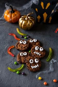 Современный фон хэллоуина. печенье на хэллоуин. забавные монстры из печенья с шоколадом на столе