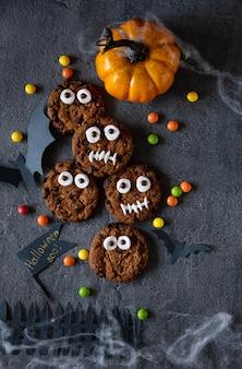 現代のハロウィーンの背景。ハロウィーンのクッキー。テーブルの上のチョコレートとビスケットで作られた面白いモンスター