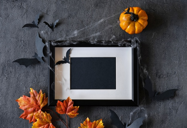 Modern halloween background with pumpkins, bats and black frame on dark background