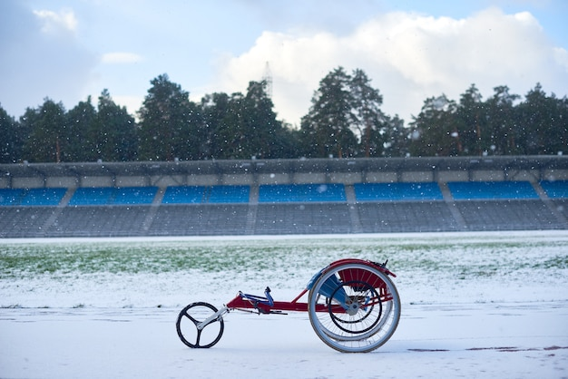 Modern handcycle for paraplegic athletes standing at track and field stadium on snowy winter day