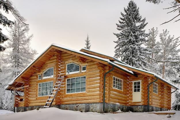 Современный бревенчатый дом ручной работы с большими окнами в снегу зимой.
