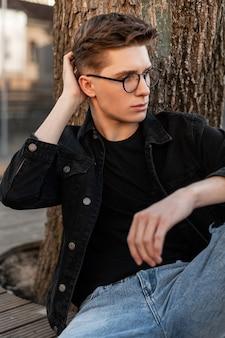 세련된 청바지 옷에 현대 잘 생긴 젊은 남자가 야외에서 유행 헤어 스타일을 곧게 만듭니다