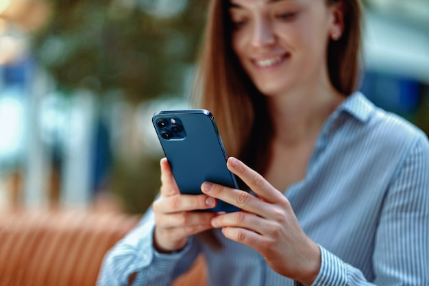 Modern happy attractive casual smiling smart millennial woman using phone for online browsing and chatting