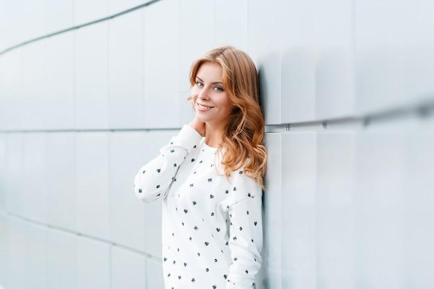 明るいモダンな壁の近くの街でスタイリッシュな白いセーターで美しい笑顔とモダンな幸せなポジティブな若い女性